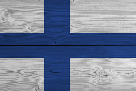 Finland flag painted on old wood plank. Patriotic background. National flag of Finland