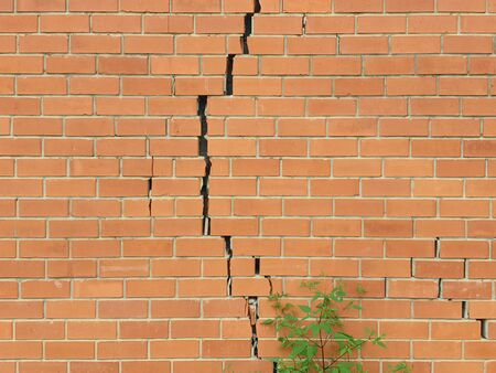 Cracked brick wall. Broken brick wall background Imagens