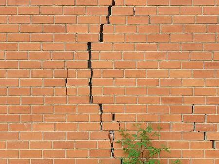 Mur de brique fissuré. Fond de mur de briques cassées