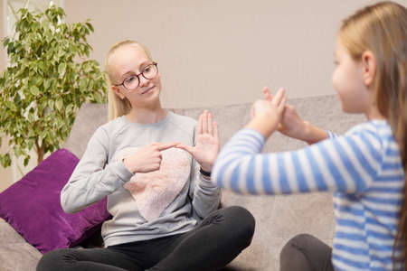 two deaf girls talking gestures on sofa. high quality Stock Photo