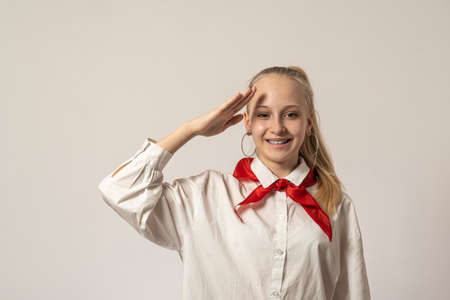 Teenage girl with bologna hair and pioneer tie on a light background raise her hand