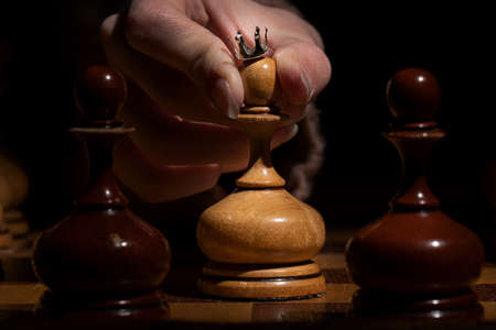 female hand holds a pawn with a crown on a dark background. old chess. business concept.