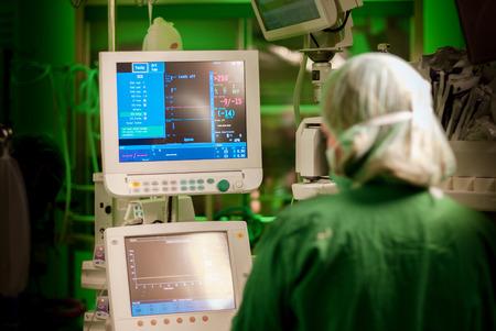 female anaesthesiologist at monitor in operation surgery room with green lights on