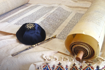 The Hebrew handwritten Torah, on a synagogue alter, with Kippah and Talith Stock Photo