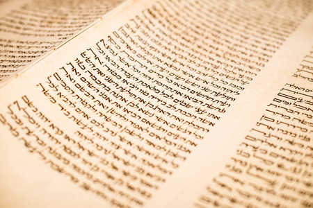 The Hebrew handwritten Torah, on a synagogue alter, illustrating Jewish holidays, during fests. Letters of scriptures close up.
