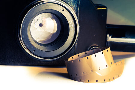 16mm: Film strips closeup with vintage movie cinema camera with lens on background