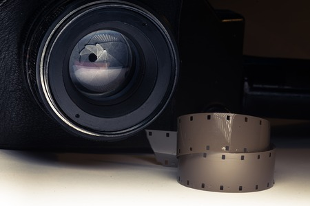 cine: Film strips closeup with vintage movie cinema camera in shadow on background
