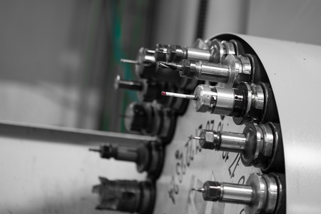 Rotating head with drilling machine bits and tools in a high precision mechanics plant at CNC lathe in workshop Standard-Bild