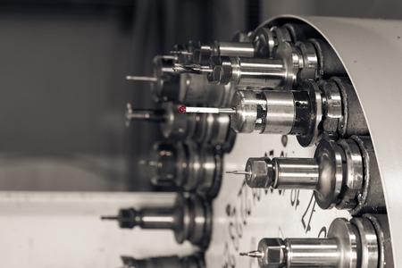 herramientas de mecánica: Rotación de la cabeza con los bits y herramientas de perforación de la máquina en una planta mecánica de alta precisión en torno CNC en el taller