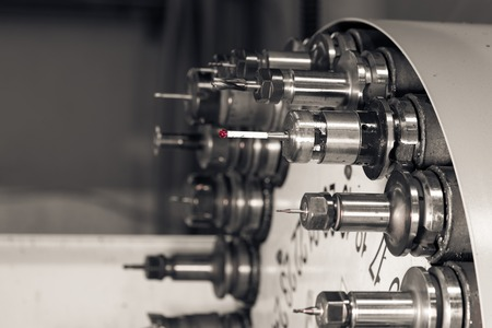 Rotating head with drilling machine bits and tools in a high precision mechanics plant at CNC lathe in workshop Stockfoto