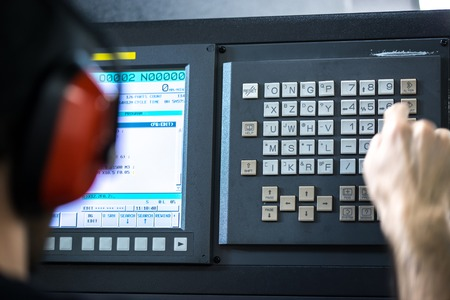milling center: CNC operator, mechanical technician worker at metal machining milling center in tool workshop inserting data with keyboard wearing noise cancelling headset Archivio Fotografico