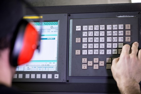 setup operator: CNC operator, mechanical technician worker at metal machining milling center in tool workshop inserting data with keyboard wearing noise cancelling headset Stock Photo