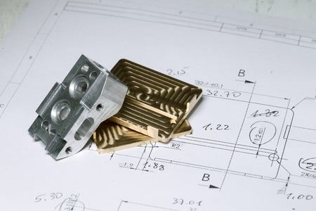 Ready CNC golden and silver metal detail on technical drawing sketch with measures