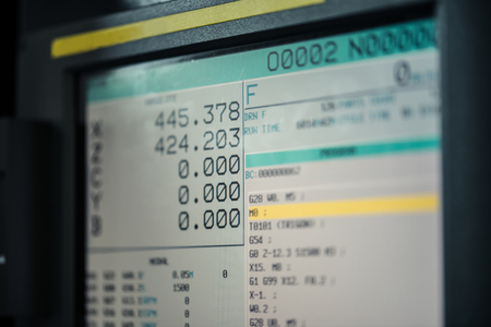 CNC machine monitor display with program code running and numbers with parameters changing Standard-Bild