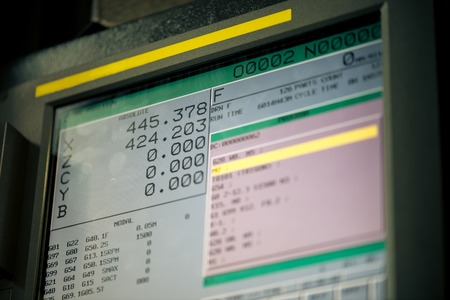 ncc: CNC machine monitor display with program code running and numbers with parameters changing Stock Photo