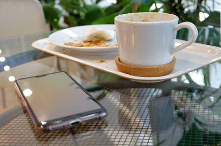 Breakfast at the cafe. On the glass table dirty dishes - a coffee cup and a plate with crumbs from eaten croissant - and a smartphone. Horizontal orientation. Selective focus. Blurred background. Stock Photo