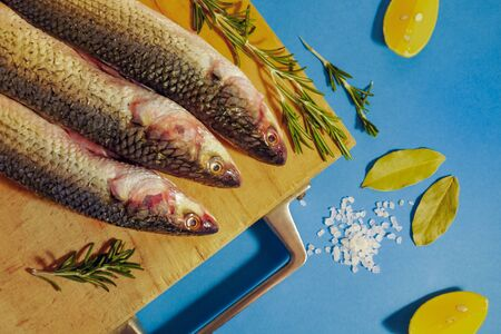 Fresh healthy low-calorie mullet fish on a wooden cutting board with rosemary, lemon and sea salt. Blue background. Horizontal orientation, selective focus.