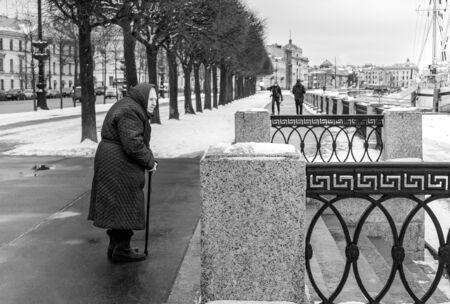 Russia, St. Petersburg. February 09, 2020. An old woman stands and looks forward for a walk in winter, early spring. Old age, lonely old age concept. Horizontal orientation. Black and white.