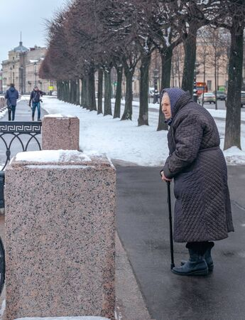 Russia, St. Petersburg. February 09, 2020. An old woman stands and looks forward for a walk in winter, early spring. Old age, lonely old age concept. Vertical orientation.