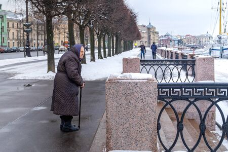 Russia, St. Petersburg. February 09, 2020. An old woman stands and looks forward for a walk in winter, early spring. Old age, lonely old age concept. Horizontal orientation.