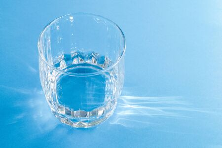 A glass with clean clear clear water, illuminated by bright sunlight, stands on a blue surface. Hard light. Horizontal orientation.