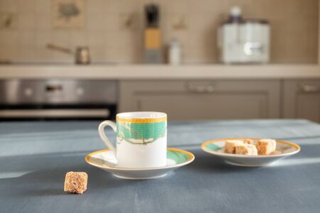A small beautiful coffee cup stands on a dark gray surface on a blurry background of the interior of a cozy kitchen on a sunny morning or day. Next to a saucer with pieces of cane sugar.