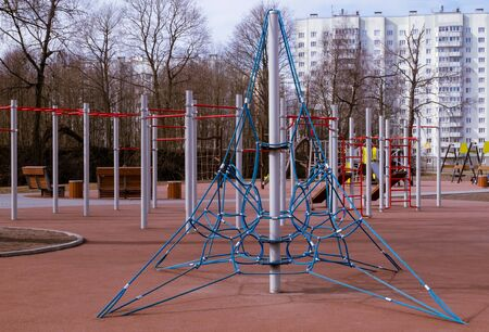Empty playground with swings and sports simulators for preschool and early school-age children in a residential area. Sunny day in early spring or late autumn. Horizontal orientation. Selective focus