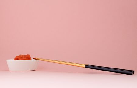 Marinated ginger and chopsticks with black handles, folded cross on a pink background. Flat lay with copy space, selective focus. Japanese food. Horizontal orientation.