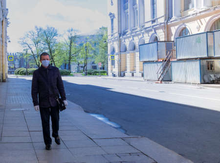 A middle-aged Caucasian man wearing a mask and gloves walks down an empty street in the city during the COVID-19 quarantine. Quarantine by COVID-19 concept. Horizontal orientation, selective focus.