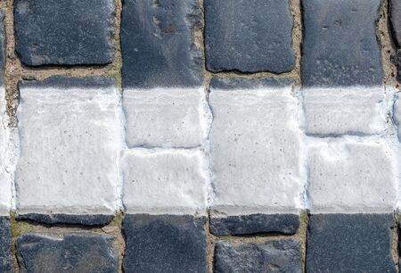 Fragment of a cobblestone pavement with a white strip of road markings, painted with special paint. Horizontal orientation, selective focus.