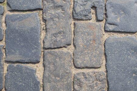 Fragment of a old cobblestone pavement. Horizontal orientation, selective focus.