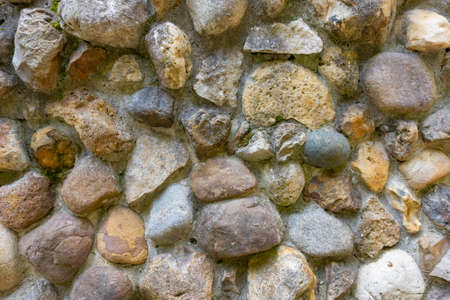 Fragment of an ancient wall made of natural stone. Horizontal orientation, selective focus.