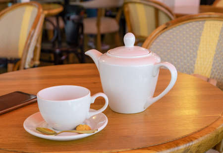 White porcelain teapot, tea cup and smartphone stand on a table in a cafe. Horizontal orientation, selective focus. Stockfoto