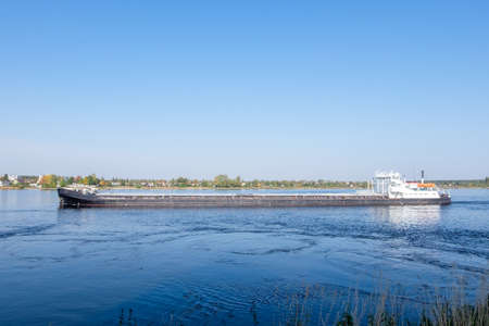 Commercial dry cargo ship sails along the river in summer or early autumn. Horizontal orientation, selective focus. Stock fotó