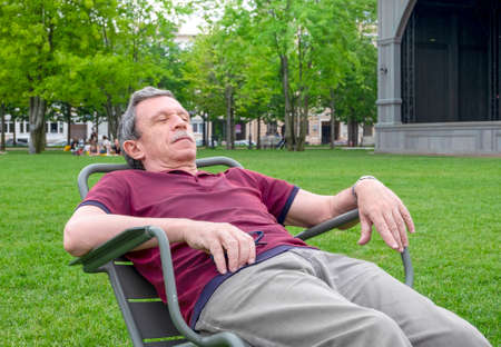 Close-up of a senior retired adult relaxing on a sun lounger in a public park on a summer day. Comfortable urban environment. Horizontal orientation, selective focus.