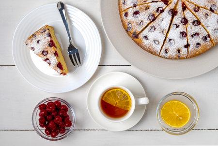 Top view close-up of sliced cherry pie, slice of pie on a plate and lemon tea. Selective focus, horizontal orientation. Foto de archivo
