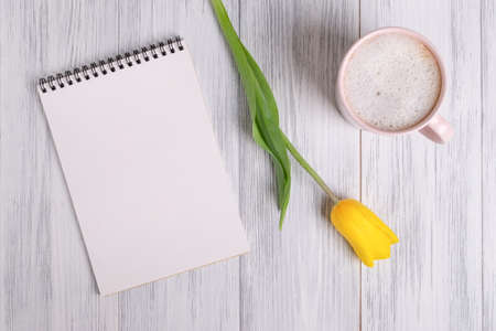 Top view of a mockup of a blank notepad, a cup of coffee or cocoa and a yellow tulip on a light painted wooden surface. Selective focus. Copy space.