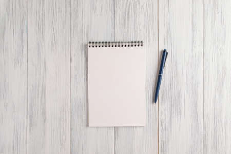 An overhead view of a mockup of a blank notepad and an automatic ballpoint pen on a light painted wooden surface. Selective focus. Copy space.