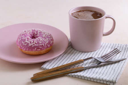 Two sugar-coated donuts lie on a pink ceramic plates. Serving with cutlery, mug of coffee and linen napkin. Selective focus.