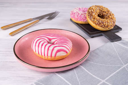 Three sugar-coated donuts lie on a pink ceramic plate and a slate board. Serving with cutlery and linen napkin. Selective focus. Stockfoto