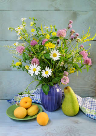 Bouquet of wildflowers: clover, daisies, vetch, aster, clover, etc. in a purple ceramic vase, a saucer dish with apricots, a green pear on a blue plank background.