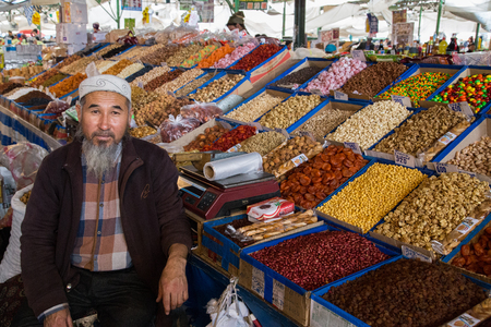 bazar: Bishkek, Kyrgyzstan - October 2, 2014: A dried fruits vendor with his shop at Osh Bazar