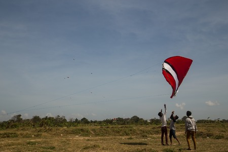 gigantic: Sanur, Bali, Indonesia - July 19, 2015: A group of people is starting a gigantic kite at Sanur Beach.