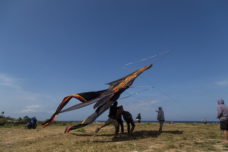 sanur: Sanur, Bali, Indonesia - July 19, 2015: A group of people is starting a gigantic kite at Sanur Beach.