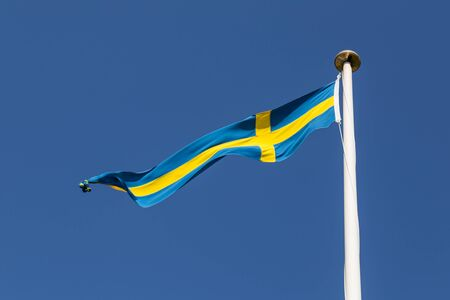 the swedish flag: Photograph of a long and thin Swedish flag. Stock Photo