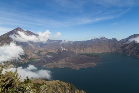 the height of a rim: Phtograph of the huge crater lake of volcano Mount Rinjani. The small volcano Gunung Baru inside the crater has been formed by eruptions. Stock Photo