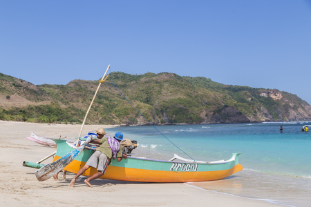 indonesia culture: Kuta, Lombok, Indonesia - July 16, 2015: Two fisherman on the beach are pushing a fishing boat into the ocean to go fishing. Editorial
