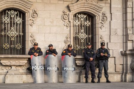 central government: Lima, Peru - September 05, 2015: Five policemen are guarding the central square in front of the government palace on a Saturday afternoon.