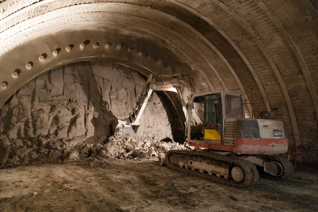 Geneva, Switzerland - May 22, 2014: An excavator digging the front of a tunnel.