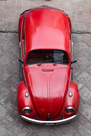 mini car: Arequipa, Peru - October 16, 2015: Top view of a red Volkswagen Kaefer in the roads of Arequipa.
